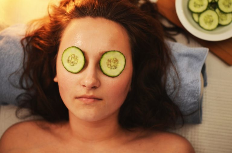 Women laying down with cucumber slices on her eyes